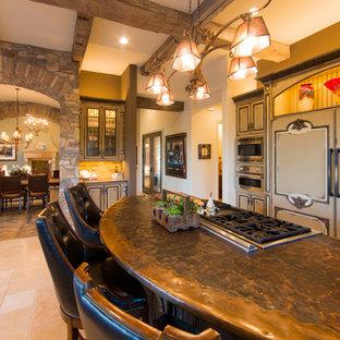 Idee per una cucina lineare mediterranea chiusa e di medie dimensioni con ante a filo, ante beige, top in rame, paraspruzzi beige, paraspruzzi con piastrelle in pietra, elettrodomestici da incasso, pavimento in travertino e isola
