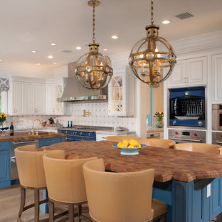 Large traditional eat-in kitchen inspiration - Inspiration for a large timeless l-shaped medium tone wood floor and brown floor eat-in kitchen remodel in Phoenix with raised-panel cabinets, white cabinets, wood countertops, multicolored backsplash, colored appliances, two islands, brown countertops and a farmhouse sink