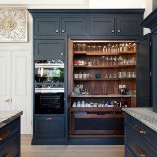Exempel på ett klassiskt vit vitt kök och matrum, med luckor med profilerade fronter, marmorbänkskiva, spegel som stänkskydd, rostfria vitvaror, ljust trägolv och en köksö