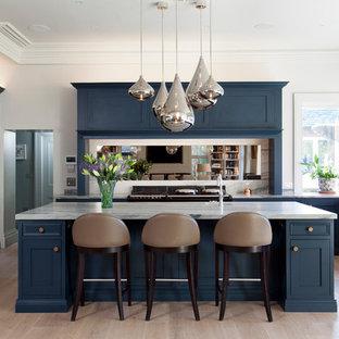 Klassisk inredning av ett vit vitt kök, med luckor med profilerade fronter, marmorbänkskiva, spegel som stänkskydd, ljust trägolv, en köksö, blå skåp, svarta vitvaror och beiget golv