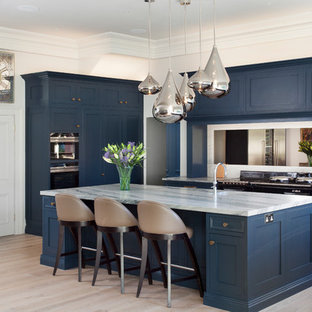Design ideas for a traditional kitchen/diner in Cheshire with beaded cabinets, marble worktops, mirror splashback, stainless steel appliances, light hardwood flooring, an island and white worktops.