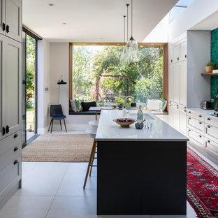 Diseño de cocina contemporánea, grande, abierta, con encimera de acrílico, salpicadero gris, una isla, suelo gris, fregadero bajoencimera, armarios con paneles empotrados, puertas de armario grises y encimeras blancas
