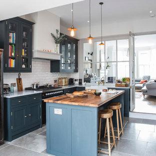 Mittelgroße Klassische Wohnküche in L-Form mit Landhausspüle, Schrankfronten im Shaker-Stil, Arbeitsplatte aus Holz, Kalkstein, Kücheninsel, blauen Schränken, grauem Boden, Küchenrückwand in Weiß und Rückwand aus Metrofliesen in London