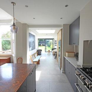 Imagen de cocina en L, moderna, de tamaño medio, abierta, con armarios con paneles lisos, puertas de armario grises, encimera de cobre, suelo de baldosas de porcelana, una isla, suelo gris y encimeras marrones