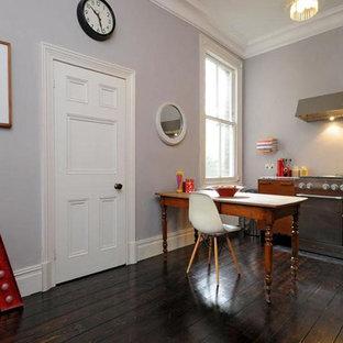 ロンドンの大きいエクレクティックスタイルのおしゃれなキッチン (ドロップインシンク、フラットパネル扉のキャビネット、中間色木目調キャビネット、ステンレスカウンター、茶色いキッチンパネル、木材のキッチンパネル、シルバーの調理設備の、濃色無垢フローリング、アイランドなし、黒い床) の写真