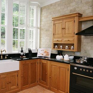 Immagine di una cucina a L country chiusa con ante con bugna sagomata, ante in legno scuro, top in onice e paraspruzzi nero