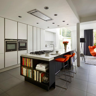 Inspiration for a modern galley open plan kitchen in Manchester with flat-panel cabinets, white cabinets, stainless steel appliances, an island and grey floors.