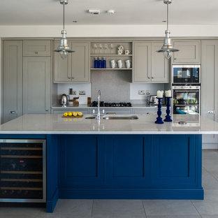 Diseño de cocina de galera, clásica renovada, grande, abierta, con fregadero integrado, armarios con paneles empotrados, puertas de armario grises, encimera de cuarzo compacto, salpicadero verde, suelo de baldosas de porcelana y una isla