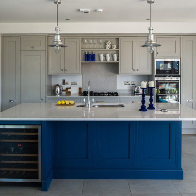 Inspiration for a large transitional galley porcelain tile open concept kitchen remodel in Dublin with an integrated sink, recessed-panel cabinets, gray cabinets, quartz countertops, gray backsplash and an island