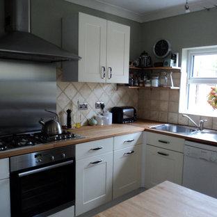 ロンドンの小さいエクレクティックスタイルのおしゃれな独立型キッチン (木材カウンター、磁器タイルのキッチンパネル、シルバーの調理設備、テラコッタタイルの床、赤い床) の写真