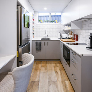 Photo of a small contemporary u-shaped eat-in kitchen in Sydney with a single-bowl sink, flat-panel cabinets, grey cabinets, quartz benchtops, white splashback, subway tile splashback, stainless steel appliances, ceramic floors, no island, brown floor and white benchtop.
