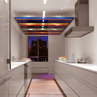 Mid-sized contemporary enclosed kitchen photos - Inspiration for a mid-sized contemporary galley light wood floor enclosed kitchen remodel in San Francisco with flat-panel cabinets, white cabinets, no island, an undermount sink, solid surface countertops, white backsplash and stainless steel appliances