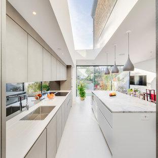 Diseño de cocina lineal, moderna, de tamaño medio, con armarios con paneles lisos, puertas de armario grises, salpicadero con efecto espejo, electrodomésticos de acero inoxidable, una isla, suelo blanco y encimeras blancas