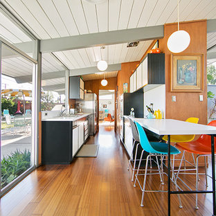 Inspiration for a mid-sized midcentury galley eat-in kitchen in Orange County with white cabinets, stainless steel appliances, medium hardwood floors and no island.