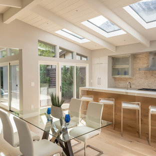 This is an example of a mid-sized midcentury eat-in kitchen in Other with glass-front cabinets, grey cabinets, concrete benchtops, beige splashback, stone tile splashback, panelled appliances, ceramic floors, brown floor and grey benchtop.
