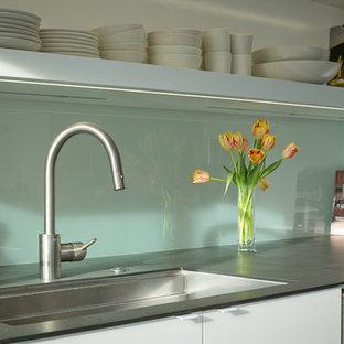 Idéer för att renovera ett retro kök, med en undermonterad diskho, släta luckor, vita skåp, vitt stänkskydd, glaspanel som stänkskydd och rostfria vitvaror