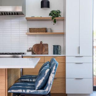 Идея дизайна: параллельная кухня среднего размера в стиле ретро с обеденным столом, накладной раковиной, плоскими фасадами, светлыми деревянными фасадами, столешницей из кварцевого агломерата, белым фартуком, фартуком из керамической плитки, техникой из нержавеющей стали, полом из керамогранита, островом, серым полом, белой столешницей и потолком из вагонки