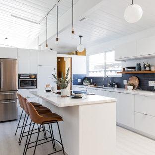 Exempel på ett mellanstort 60 tals vit vitt l-kök, med en undermonterad diskho, släta luckor, vita skåp, bänkskiva i kvarts, blått stänkskydd, stänkskydd i keramik, rostfria vitvaror, vinylgolv, en köksö och vitt golv
