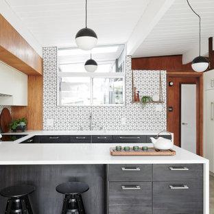 Ispirazione per una cucina ad U minimalista con lavello sottopiano, ante lisce, ante grigie, paraspruzzi bianco, paraspruzzi con piastrelle a mosaico, elettrodomestici bianchi, pavimento in cemento, penisola, pavimento grigio, top bianco, soffitto in perlinato e soffitto a volta