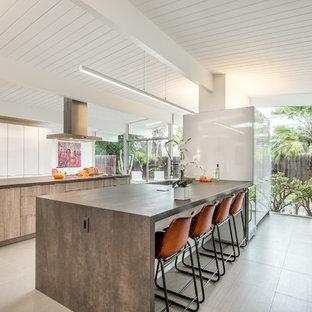 Ejemplo de cocina de galera, retro, abierta, con fregadero bajoencimera, armarios con paneles lisos, puertas de armario blancas y dos o más islas