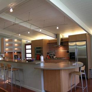 サンフランシスコの中くらいのエクレクティックスタイルのおしゃれなキッチン (アンダーカウンターシンク、フラットパネル扉のキャビネット、中間色木目調キャビネット、人工大理石カウンター、オレンジのキッチンパネル、ガラスタイルのキッチンパネル、シルバーの調理設備、無垢フローリング) の写真