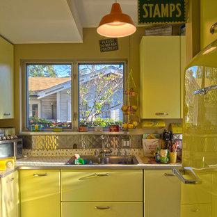Idéer för ett eklektiskt kök, med gula skåp, stänkskydd med metallisk yta och stänkskydd i metallkakel