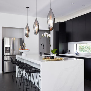 Photo of a contemporary l-shaped kitchen in Sydney with an undermount sink, flat-panel cabinets, black cabinets, white splashback, stainless steel appliances, with island, black floor and white benchtop.