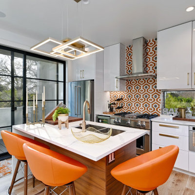 Trendy galley medium tone wood floor and brown floor kitchen photo in Austin with an undermount sink, flat-panel cabinets, white cabinets, multicolored backsplash, stainless steel appliances, an island and white countertops