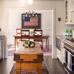 Idéer för ett klassiskt kök, med en undermonterad diskho, skåp i shakerstil, vita skåp, bänkskiva i kalksten, vitt stänkskydd, stänkskydd i tunnelbanekakel, rostfria vitvaror, mörkt trägolv och en köksö