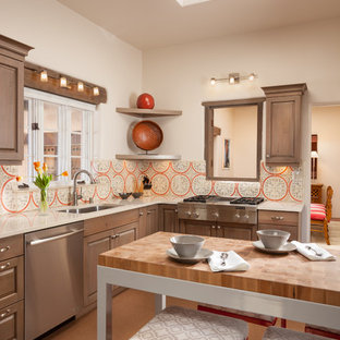 Southwestern kitchen remodeling - Inspiration for a southwestern l-shaped kitchen remodel in Albuquerque with an undermount sink, raised-panel cabinets, medium tone wood cabinets, multicolored backsplash, stainless steel appliances and an island