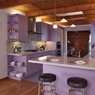 Exemple d'une cuisine américaine parallèle tendance de taille moyenne avec un évier encastré, une crédence multicolore, une crédence en carreau de verre, un électroménager en acier inoxydable, un sol gris, un placard à porte plane, des portes de placard violettes, un plan de travail en quartz modifié, une péninsule et un plan de travail violet.