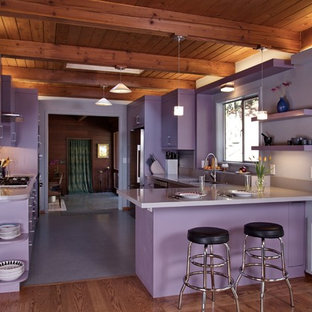 Mid-sized contemporary galley eat-in kitchen in San Francisco with an undermount sink, flat-panel cabinets, purple cabinets, quartz benchtops, multi-coloured splashback, glass tile splashback, stainless steel appliances, a peninsula, grey floor and purple benchtop.