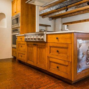 Exempel på ett mellanstort amerikanskt beige beige kök, med en undermonterad diskho, skåp i shakerstil, skåp i mellenmörkt trä, bänkskiva i kvarts, flerfärgad stänkskydd, stänkskydd i porslinskakel, rostfria vitvaror, tegelgolv, en halv köksö och rött golv