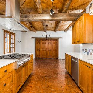 アルバカーキの中くらいのサンタフェスタイルのおしゃれなキッチン (アンダーカウンターシンク、シェーカースタイル扉のキャビネット、中間色木目調キャビネット、クオーツストーンカウンター、マルチカラーのキッチンパネル、磁器タイルのキッチンパネル、シルバーの調理設備、レンガの床、赤い床、ベージュのキッチンカウンター) の写真