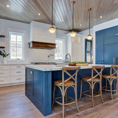 Kitchen - coastal light wood floor and beige floor kitchen idea in Los Angeles with shaker cabinets, blue cabinets, white backsplash, subway tile backsplash, paneled appliances, an island and white countertops