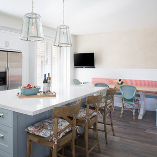 This is an example of a mid-sized beach style l-shaped eat-in kitchen in Los Angeles with a farmhouse sink, shaker cabinets, white cabinets, quartz benchtops, blue splashback, glass tile splashback, stainless steel appliances, vinyl floors and with island.