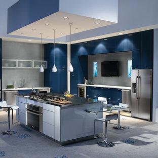 Mittelgroße Moderne Wohnküche in L-Form mit Waschbecken, flächenbündigen Schrankfronten, blauen Schränken, Edelstahl-Arbeitsplatte, Küchenrückwand in Grau, Küchengeräten aus Edelstahl, Travertin, Kücheninsel und grauem Boden in San Francisco