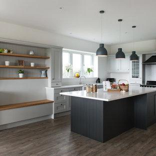 デヴォンの大きいトランジショナルスタイルのおしゃれなキッチン (エプロンフロントシンク、シェーカースタイル扉のキャビネット、グレーのキャビネット、珪岩カウンター、白いキッチンパネル、ガラス板のキッチンパネル、黒い調理設備、ラミネートの床、白いキッチンカウンター、茶色い床) の写真