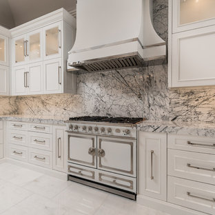This is an example of an expansive transitional u-shaped separate kitchen in Phoenix with a farmhouse sink, recessed-panel cabinets, white cabinets, marble benchtops, multi-coloured splashback, marble splashback, stainless steel appliances, marble floors, multiple islands, white floor and green benchtop.