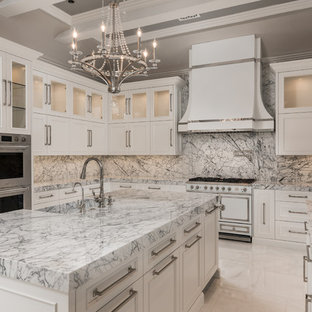 Expansive transitional u-shaped separate kitchen in Phoenix with a farmhouse sink, recessed-panel cabinets, white cabinets, marble benchtops, multi-coloured splashback, marble splashback, stainless steel appliances, marble floors, multiple islands, white floor and green benchtop.