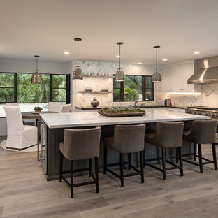 Large contemporary kitchen pictures - Large trendy u-shaped light wood floor and gray floor kitchen photo in Santa Barbara with an undermount sink, shaker cabinets, white cabinets, marble countertops, marble backsplash, stainless steel appliances, white backsplash and an island