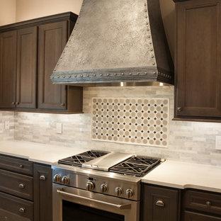 ウィチタの中サイズのインダストリアルスタイルのおしゃれなキッチン (エプロンフロントシンク、中間色木目調キャビネット、グレーのキッチンパネル、石タイルのキッチンパネル、シルバーの調理設備の、磁器タイルの床、クオーツストーンカウンター、落し込みパネル扉のキャビネット) の写真