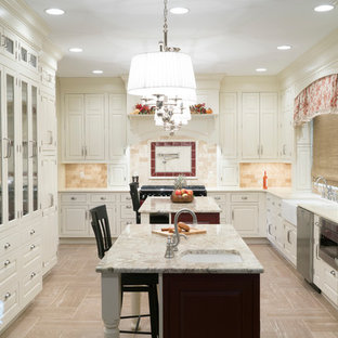 Large traditional u-shaped separate kitchen in Other with a farmhouse sink, raised-panel cabinets, white cabinets, multiple islands, stainless steel appliances, quartz benchtops, beige splashback, travertine splashback, porcelain floors and beige floor.