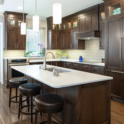 Inspiration for a mid-sized transitional l-shaped medium tone wood floor and brown floor open concept kitchen remodel in Kansas City with shaker cabinets, dark wood cabinets, quartz countertops, glass tile backsplash, an island, an undermount sink, white backsplash, stainless steel appliances and white countertops