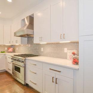 ボストンの大きいモダンスタイルのおしゃれなキッチン (アンダーカウンターシンク、シェーカースタイル扉のキャビネット、グレーのキャビネット、クオーツストーンカウンター、グレーのキッチンパネル、セラミックタイルのキッチンパネル、シルバーの調理設備の、無垢フローリング、黄色い床、白いキッチンカウンター) の写真