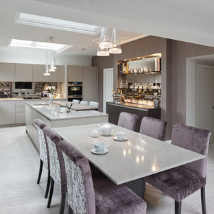 Inspiration for a large traditional l-shaped kitchen/diner in Other with a built-in sink, flat-panel cabinets, beige cabinets, quartz worktops, brown splashback, mirror splashback, black appliances, porcelain flooring, an island and grey floors.