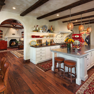 Large mediterranean eat-in kitchen appliance - Example of a large tuscan medium tone wood floor eat-in kitchen design in Santa Barbara with white cabinets, multicolored backsplash, stainless steel appliances, an island and open cabinets