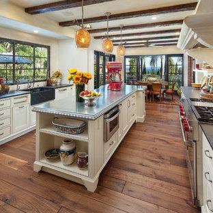 Idéer för ett stort medelhavsstil kök, med en rustik diskho, luckor med infälld panel, vita skåp, bänkskiva i täljsten, flerfärgad stänkskydd, stänkskydd i mosaik, rostfria vitvaror, mörkt trägolv och en köksö