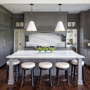 Immagine di una cucina classica con lavello sottopiano, ante con riquadro incassato, ante grigie, paraspruzzi bianco, paraspruzzi in lastra di pietra, elettrodomestici da incasso, parquet scuro, isola, pavimento marrone e top bianco