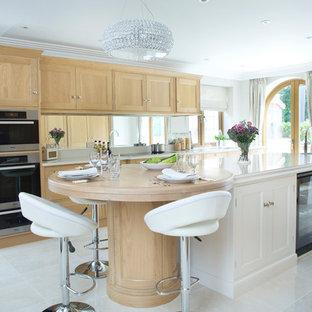 Klassische Küche mit Schrankfronten mit vertiefter Füllung, hellen Holzschränken, Arbeitsplatte aus Holz, Rückwand aus Spiegelfliesen, schwarzen Elektrogeräten, Kücheninsel, beigem Boden und beiger Arbeitsplatte in Kent